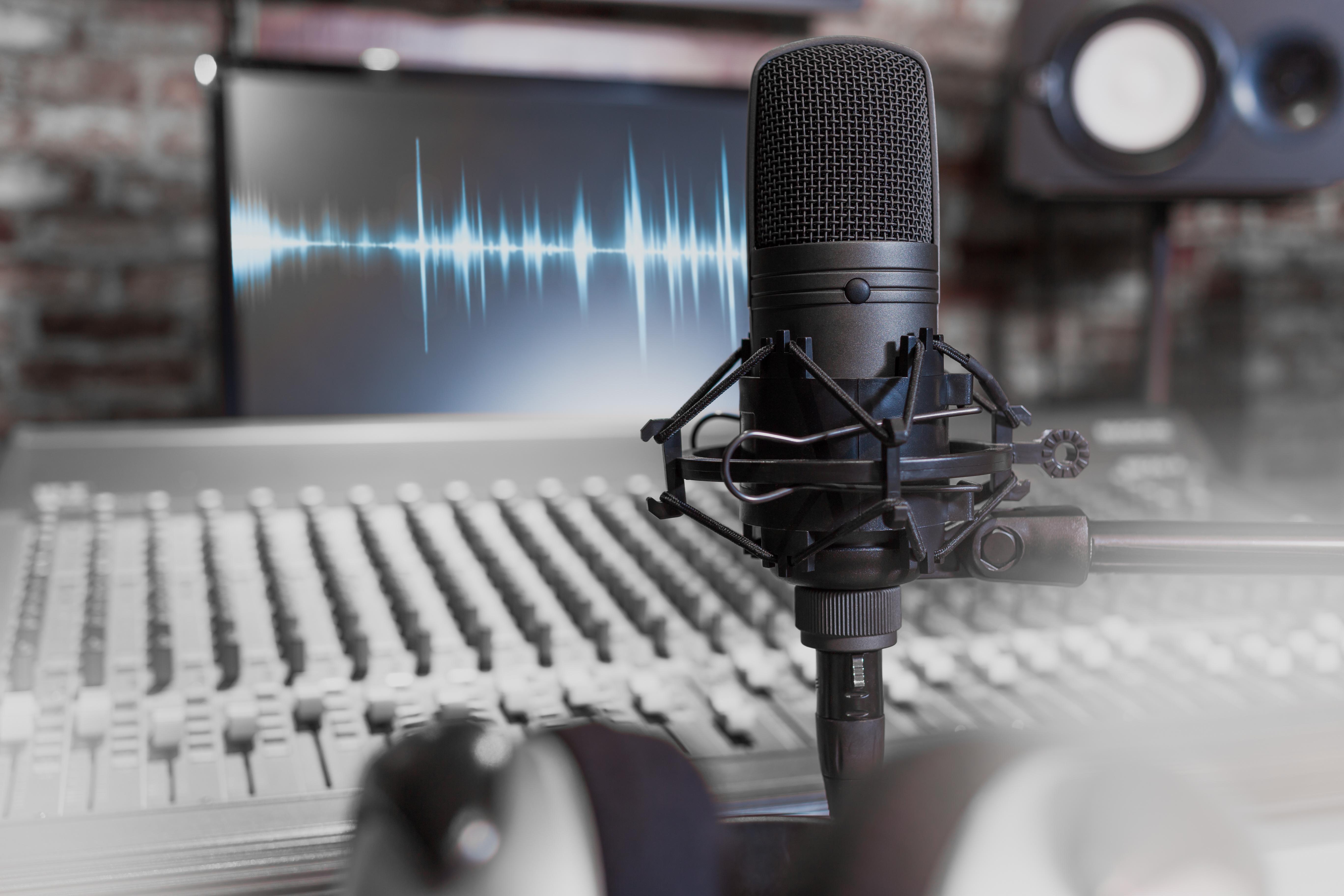 Foto eines Studio-Arbeitsplatzes mit Mischpult, Mikrofon und Computermonitor