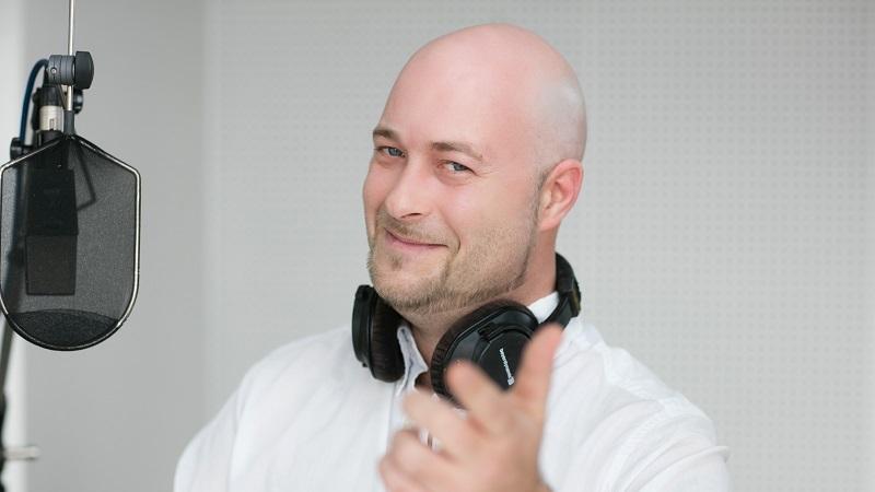 Portraitfoto von Mike Weber - Moderator, Redakteur. Produzent, mit Kopfhörer und Mikrofon